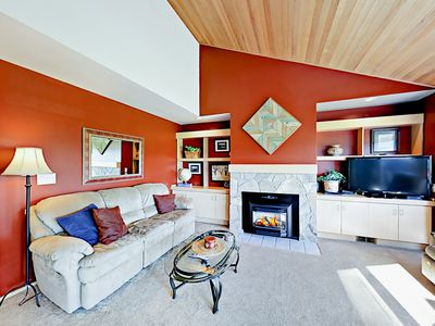 """Living Room - The living room is furnished with tasteful decor, a gas fireplace, a plush couch, and a 47"""" TV."""