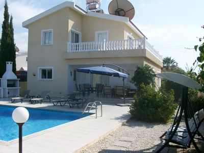Rear view of villa with secluded garden, spacioussunbathing areas & large pool