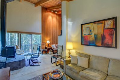 Living room with seating, wood stove, and artistic decor
