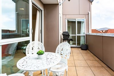 The house includes a private balcony with a BBQ and patio seating area.