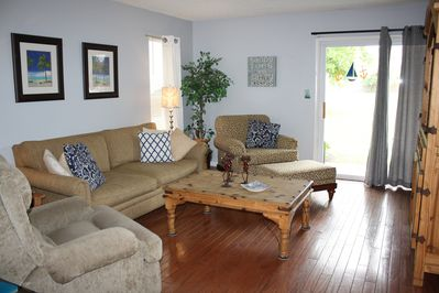 Spacious living area with flatscreen Smart tv and exit to back porch.