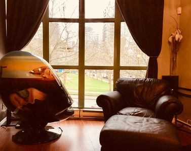 Living room floor to ceiling windows overlook park with Salvador Dali Egg chair