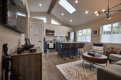 Bright open concept living area with vaulted ceilings and skylight