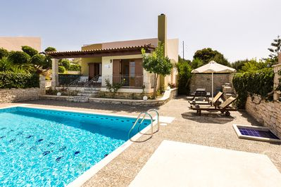 Outdoor area of our villa with pool, sun beds, barbecue & sitting areas