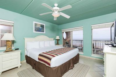 The master bedroom has a king-size bed and a beautiful view of the ocean.