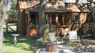 Rear of cabin showing enclosed porch and fire pit.