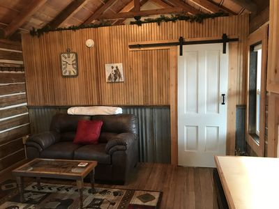 Living room with sliding barn door leading to bedroom