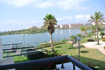 view from balcony overlooking gardens, pool and lake