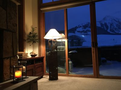 Cozy corner with fireplace and night mountain views