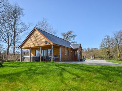Photo for This quality lodge with hot tub offers seclusion, countryside views and a cosy interior with wood bu