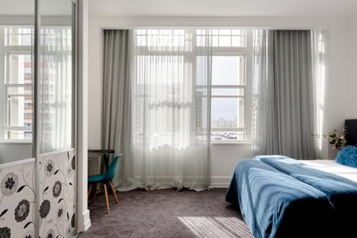 Sleep: Bedroom with desk, wardrobe and a small harbour view.