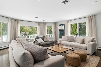 The living room has ample seating and is surrounded by the front porch