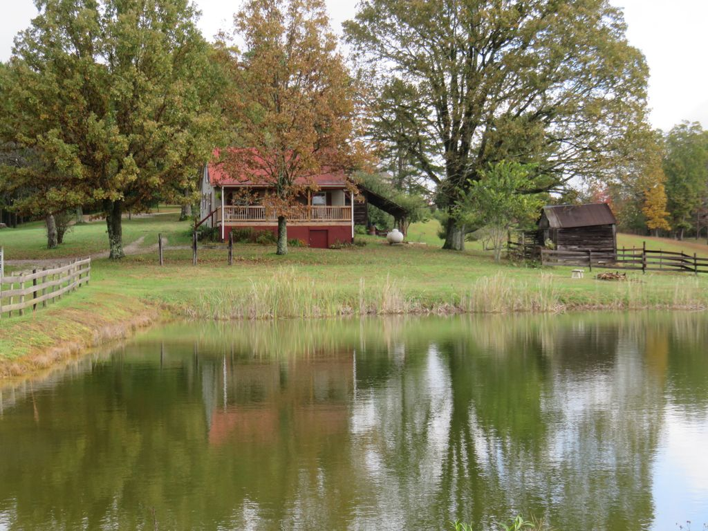 Back Of The Cabin Overlooks A Private Pond And Is Surrounded By Oak Trees.