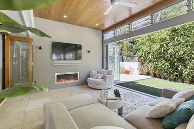 Indoor outdoor lounge room with fireplace and tv with Foxtel