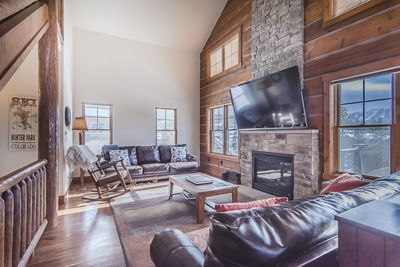 Living Area- - Living Area- Spacious area with high ceiling, fireplace, and flat screen TV.