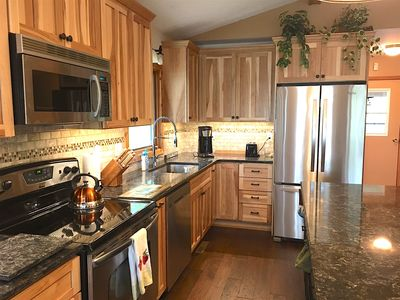 This beautiful kitchen has all stainless steel appliances and custom cupboards.