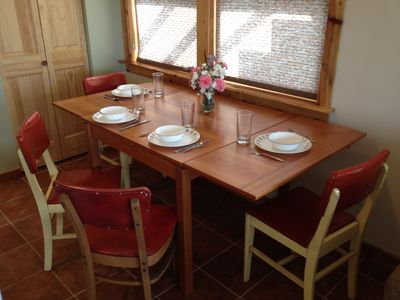 Dining room table with leaves pulled out for more spacious dining.
