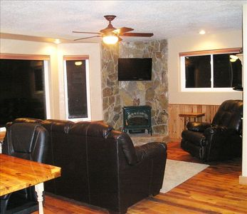 Living room features bay window, stone hearth, comfy seating, TV and work desk.