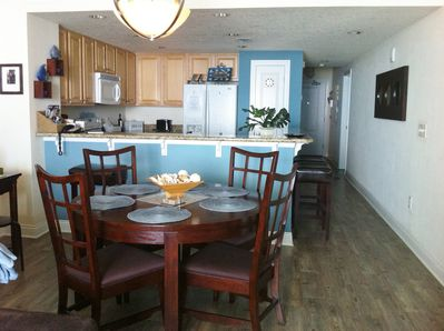 Fully equipped kitchen has breakfast bar  with stone tops and leather barstools