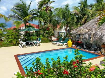 Tropical relaxation by the pool surrounded by coconut palms and flowering shrubs