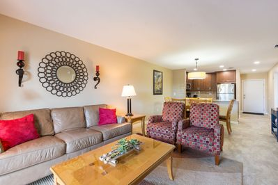 Spacious living area features a leather sofa and (2) reclining chairs