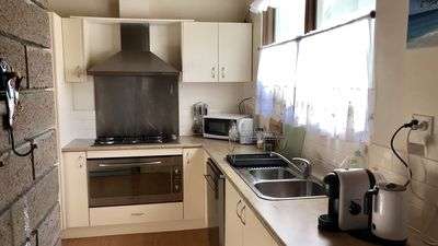 Kitchen with large fridge, upright cooker, microwave and all kitchen utensils