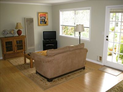 Living area with flat screen TV, love seat, garden view