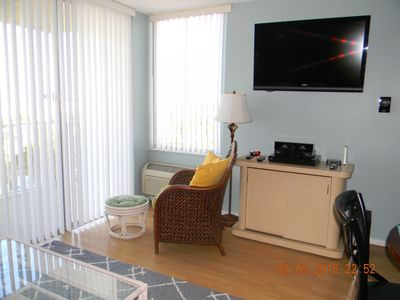 42 in. Vizio TV and comfy chair facing out towards balcony