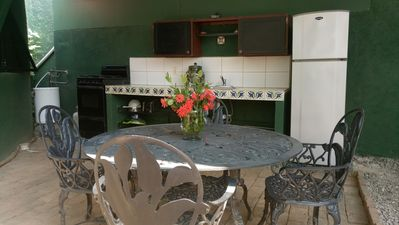 Outdoor kitchen with fridge, sink, gas stove with oven, dishes & cookware