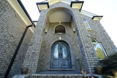 Grand front entry with iron doorway and large stairs