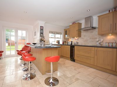 A very well equipped kitchen diner with a utility room to left and doors to enclosed garden