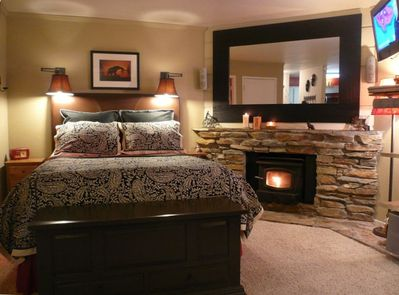 Sleeping area with queen bed, fireplace, TV