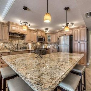 The fully stocked kitchen include granite countertops and custom cabinetry.