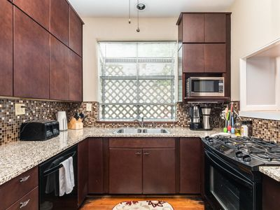 Kitchen - The kitchen features granite countertops, a mosaic tile backsplash, and a gas range.