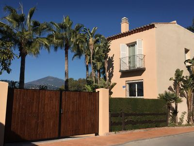 large gated garden over the full length of the house with 5 waving palmtrees