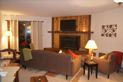 Cozy living room with wood burning fireplace, TV, and walk out patio.