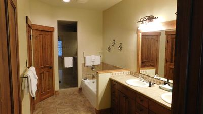 Master bathroom with dual sinks, tub and luxury shower