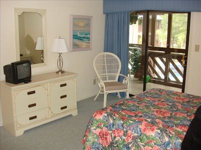 Master bedroom with queen bed has sliding  glass door to back screened porch.