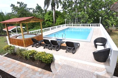 Poolside spa with swimming pool also pool furniture with BBQ pit to the left
