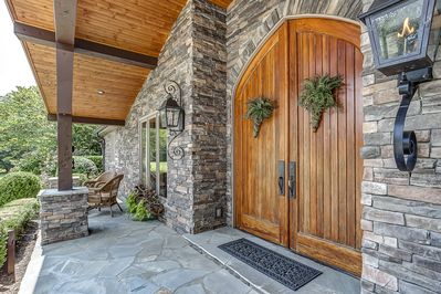 10' entry doors , stone exterior, timbers, gas lanterns, covered porch, seating