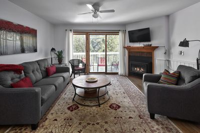 Living room with sofa bed, TV, fireplace and walkout to deck