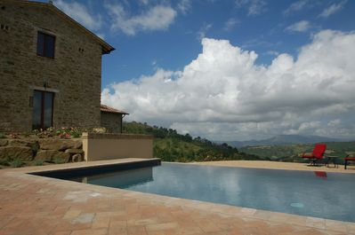 Infinity pool enjoys sun all day long. Lawn furniture, umbrellas and pool floats