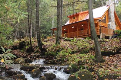 Log cabin situated by a cascading creek