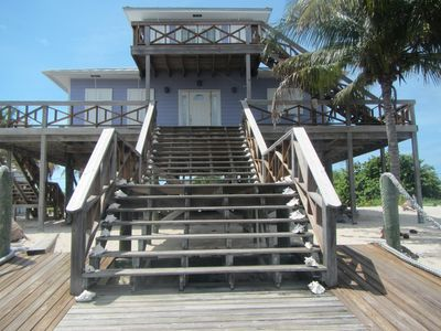 Close up view of the house showing decks surrounding the house and porches with ocean views.
