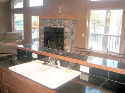 Kitchen overlooking bar and rock fireplace.  With view of river
