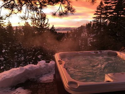 The hot tub is nestled among the boulders with a stunning view of Lake Tahoe