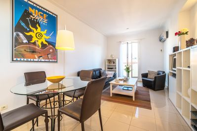 Air-conditioned lounge with dining table, sofa and entertainment centre.