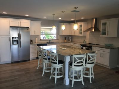 Large updated kitchen featuring large island & beautiful granite counters.