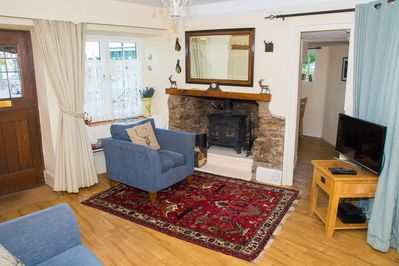 Sitting room with inglenook fireplace and inset log burner.