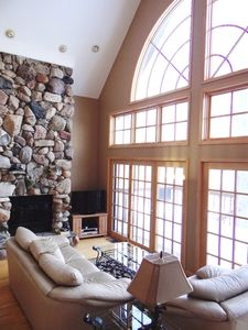 Living Room with cathedral ceiling, stone fireplace and flat screen tv